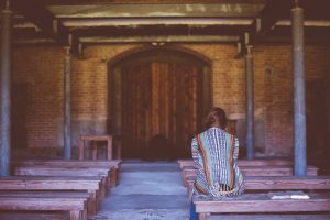 Picture of woman sitting on outdoor church pew